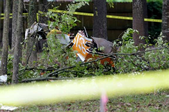 Part of the N number is visible in the wreckage of a plane crash Sunday, Oct. 25, 2020 in Woodbranch, TX. Initial reports are two are dead. The plane crashed in residential area in a wooded patch between three homes, each approximately 50 yards away from the wreckage.