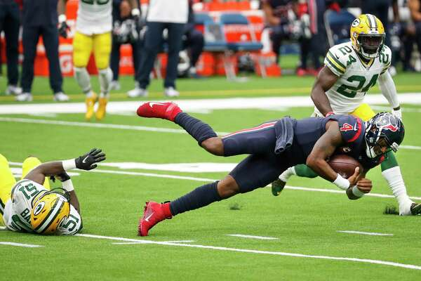 Houston Texans quarterback Deshaun Watson (4) is tripped up by Green Bay Packers inside linebacker Krys Barnes (51) after Watson was forced to scramble out of the pocket during the second quarter of an NFL football game at NRG Stadium on Sunday, Oct. 25, 2020, in Houston.