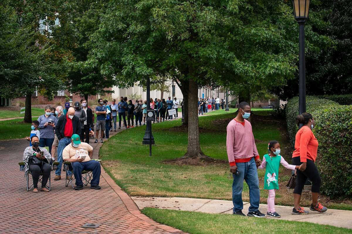 Voters stand and sit in line for early voting on Monday morning, Oct. 12, 2020, at Agnes Scott College in Decatur, Ga. (Nicole Craine/The New York Times)