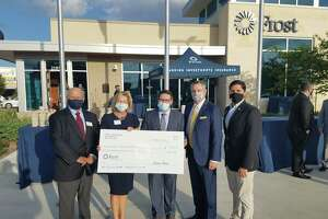 Representatives from the Ballard House accept a $5,000 donation from Frost Bank on Oct. 22, 2020.