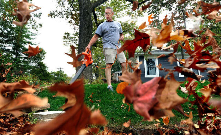 Brian Stanley uses a leaf blower to move leaves into piles at his home on Allen Street in Edwardsville on Oct. 18. Photo: Thomas Turney | For The Intelligencer