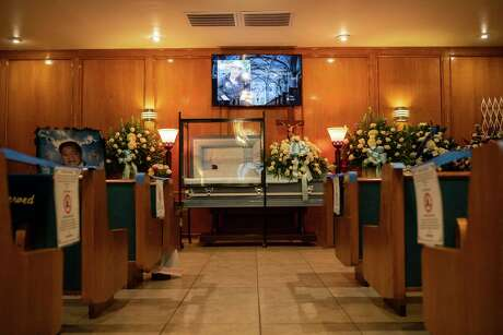The body of Francisco Tafolla Sr. behind a plexiglass shield during a visitation at Salinas Funeral Home in Elsa, Texas, July 21, 2020. The death toll from the coronavirus in the Rio Grande Valley is forcing funeral directors to buy refrigerated trucks and bypass traditional services such as velorios. (Tamir Kalifa/The New York Times)