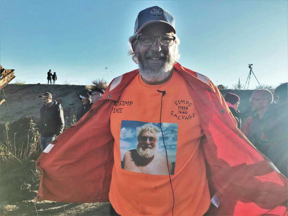 Mike Oberloier opens his jacket to reveal his trademark orange shirt with his late father's photograph on it. (Lori Qualls/Daily News)