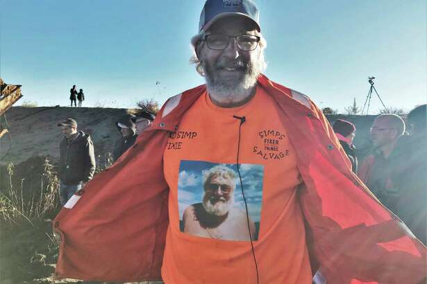 """Mike Oberloier opens his jacket to reveal his trademark orange shirt with a photograph of his late father, Bill """"Moose"""" Oberloier. (Lori Qualls/Daily News)"""