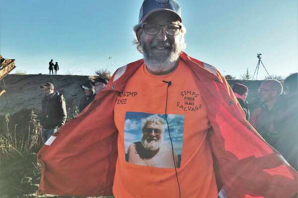 "Mike Oberloier opens his jacket to reveal his trademark orange shirt with a photograph of his late father, Bill ""Moose"" Oberloier. (Lori Qualls/Daily News)"