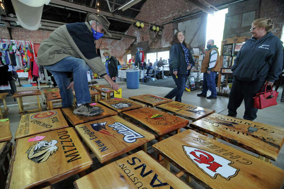 """Melvin Harris of Bethalto marks a hand-made bench as """"sold"""" for a customer who wants to do a little more shopping Sunday during the monthly flea market at The Loading Dock in Grafton. The popular tourist attraction ended its virus-shortened season this weekend, with plans to return in April 2021"""