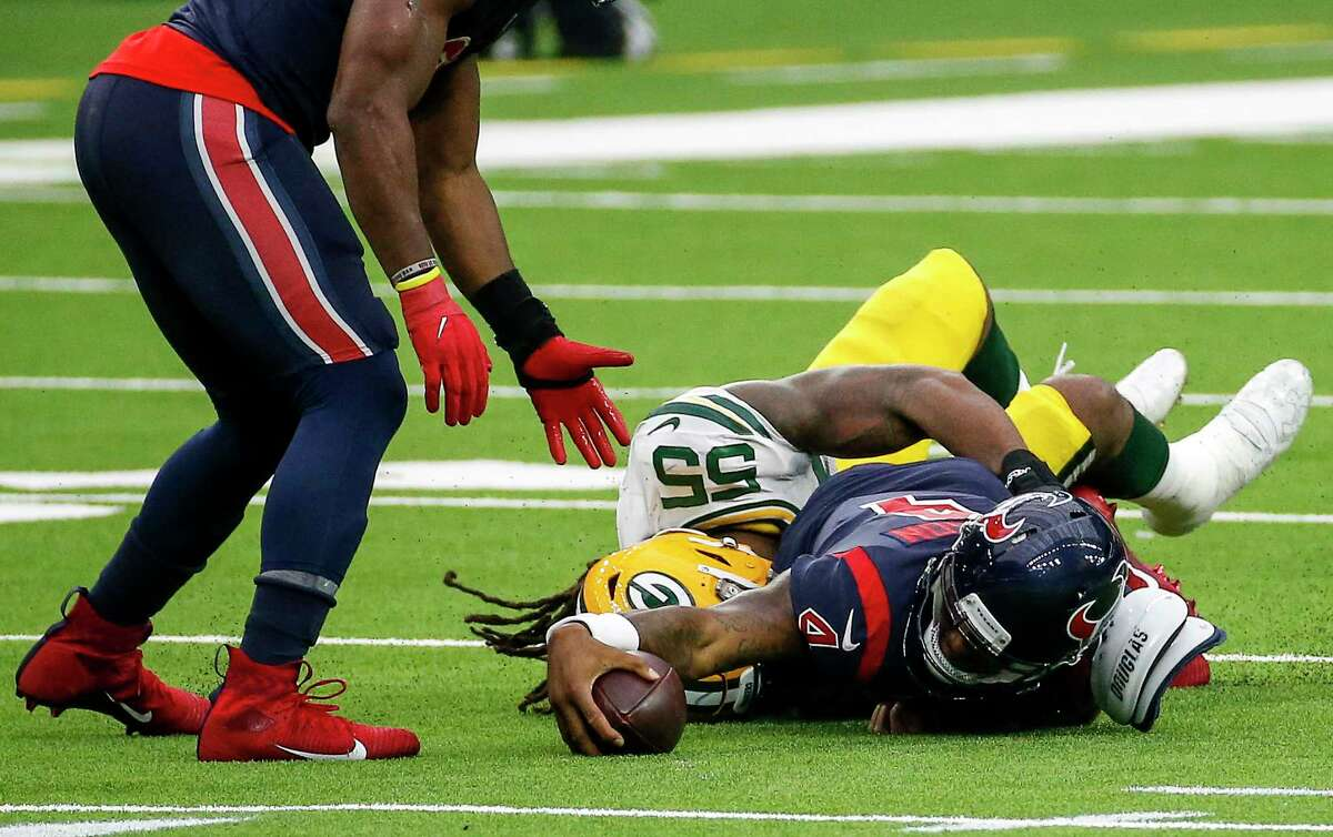 Houston Texans quarterback Deshaun Watson (4) reaches as he is tackled by Green Bay Packers outside linebacker Za'Darius Smith (55) during the fourth quarter of an NFL game Sunday, Oct. 25, 2020, at NRG Stadium in Houston.