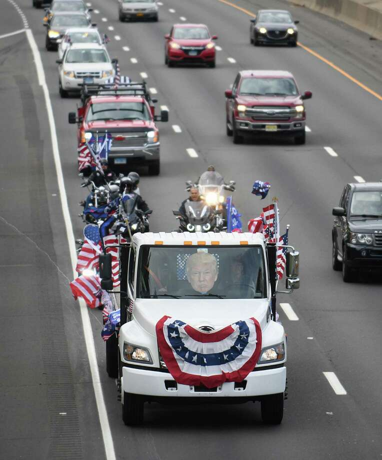 A truck with a large cutout head of Donald Trump leads the Trump caravan north on I-95 as part of the Trump 2020/Back the Blue rally in Greenwich, Conn. Sunday, Oct. 25, 2020. Hundreds of Donald Trump supporters rallied together to how support for the president's re-election bid in the Island Beach parking lot before caravaning north together on I-95. Photo: Tyler Sizemore / Hearst Connecticut Media / Greenwich Time