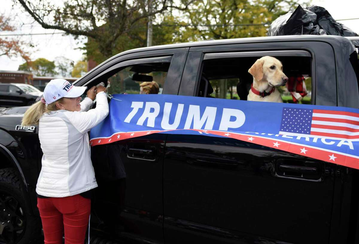 Greenwich's Beth MacGillivray hangs a Trump banner as a dog, Tenley, looks out the window during the Trump 2020/Back the Blue rally in Greenwich, Conn. Sunday, Oct. 25, 2020. The event was put together by members of a Facebook group called Make America Great Women's Group and was promoted entirely by social media as a grass-roots effort leading up to next week's election day where President Donald Trump is being challenged by former Vice President Joe Biden. DeLuca stressed that the group was made up of