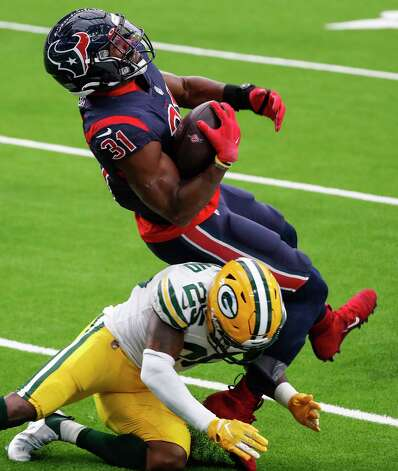 Houston Texans running back David Johnson (31) is tripped up by Green Bay Packers safety Will Redmond (25) during the second half an NFL football game at NRG Stadium on Sunday, Oct. 25, 2020, in Houston. Photo: Brett Coomer, Staff Photographer / © 2020 Houston Chronicle