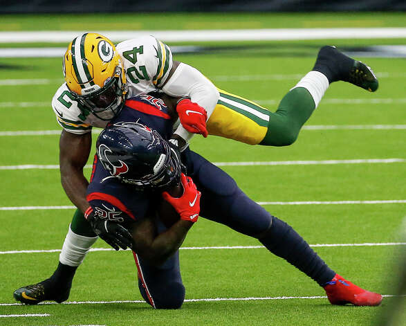 Houston Texans running back Duke Johnson (25) is tackled by Green Bay Packers safety Raven Greene (24) during the third quarter of an NFL game Sunday, Oct. 25, 2020, at NRG Stadium in Houston. Photo: Jon Shapley, Staff Photographer / © 2020 Houston Chronicle