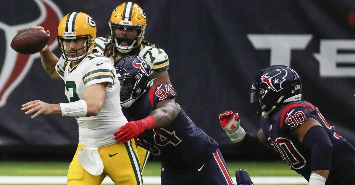 Green Bay Packers quarterback Aaron Rodgers (12) gets a pass off as he is pressured by Houston Texans defensive end Charles Omenihu (94) during the second half an NFL football game at NRG Stadium on Sunday, Oct. 25, 2020, in Houston.