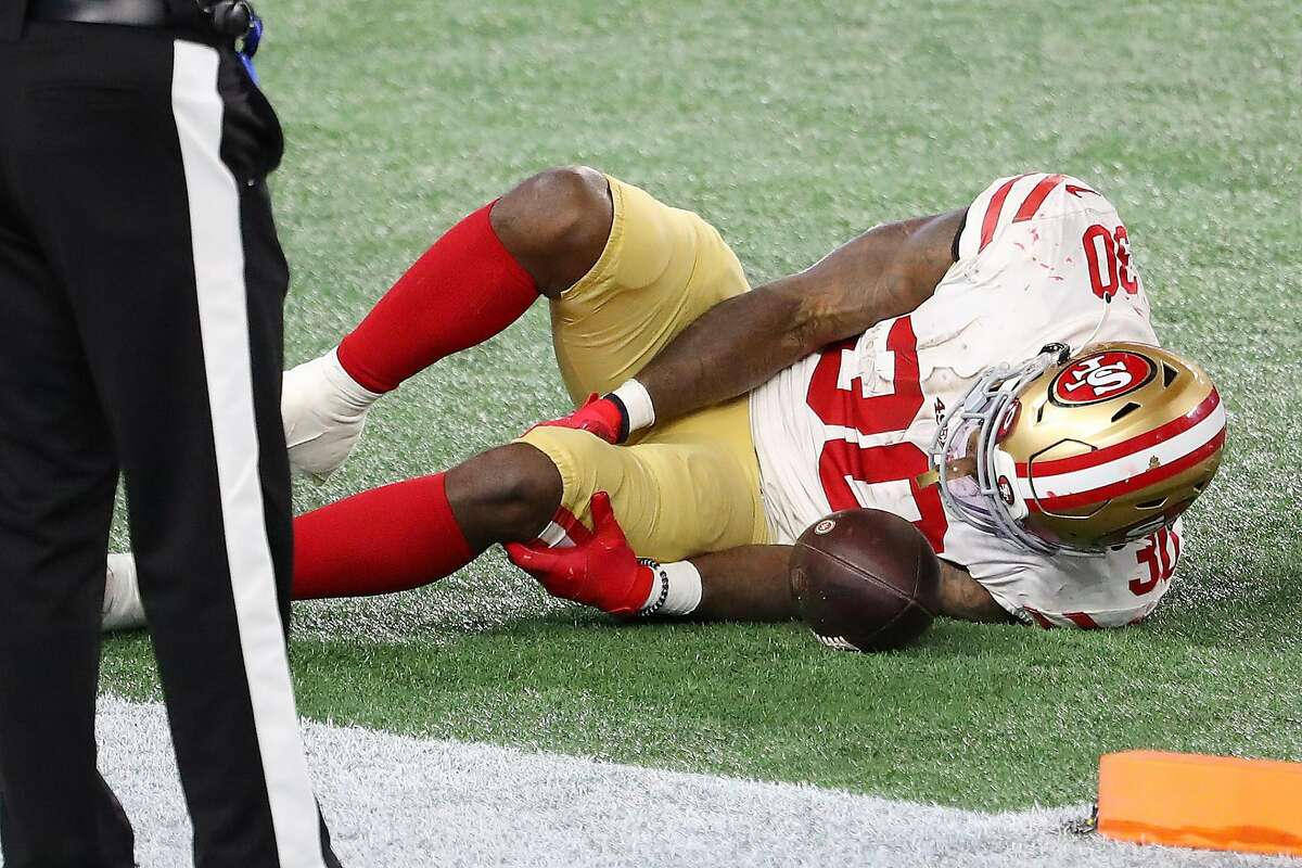 Jeff Wilson Jr. #30 of the San Francisco 49ers grabs his left leg after scoring on a seven-yard touchdown against the New England Patriots in the third quarter of their NFL game at Gillette Stadium on October 25, 2020 in Foxborough, Massachusetts.