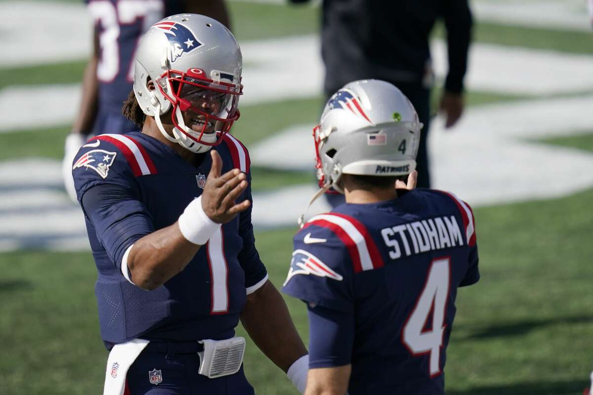 New England Patriots quarterbacks Cam Newton, left, and Jarrett Stidham speak before an NFL football game against the Denver Broncos, Sunday, Oct. 18, 2020, in Foxborough, Mass. (AP Photo/Charles Krupa)