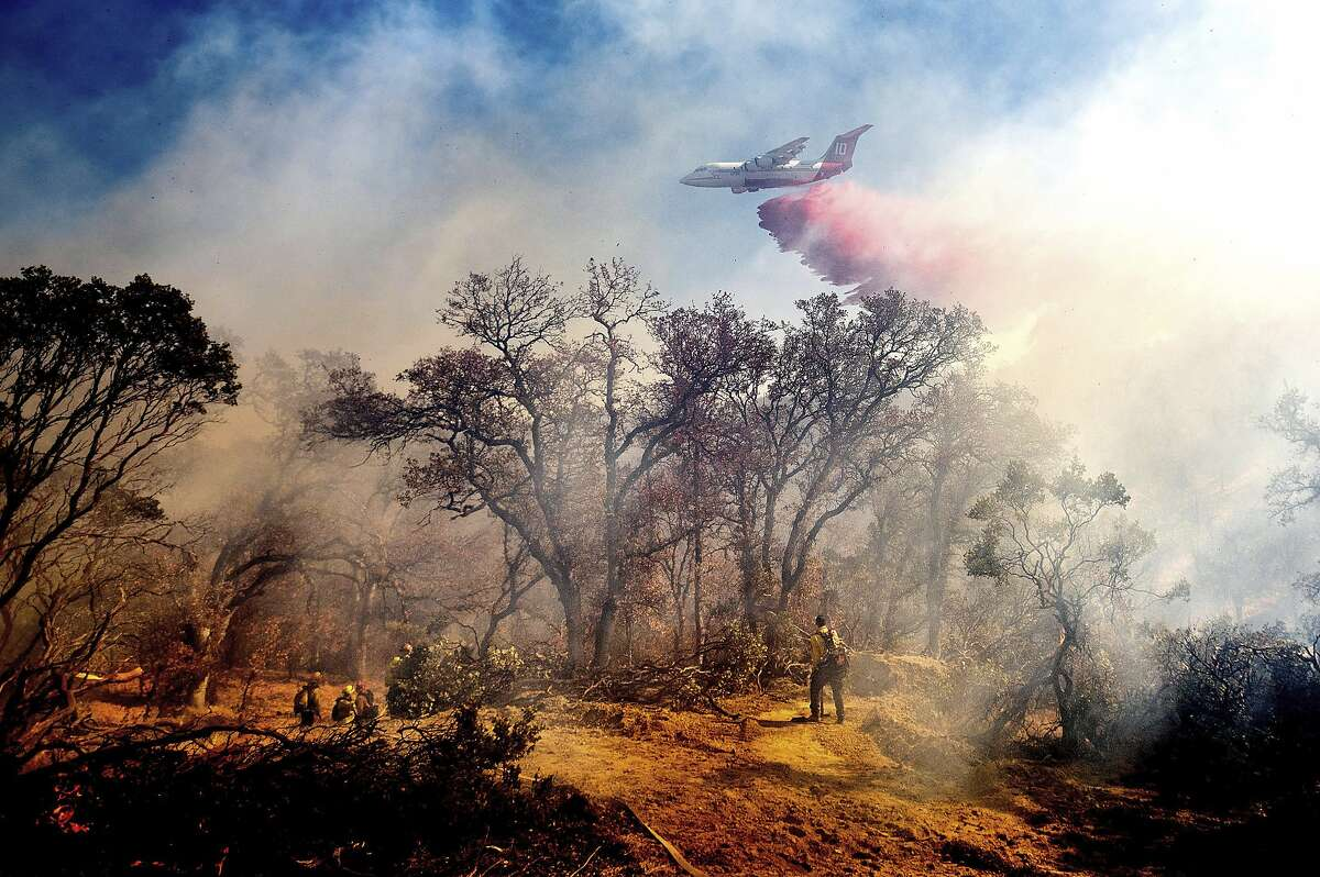 An air tanker drops retardant on the Olinda Fire burning in Anderson, Calif., Sunday, Oct. 25, 2020. The blaze was one of four fires burning near Redding that firefighters scrambled to stop as high winds buffeted Northern California. (AP Photo/Noah Berger)