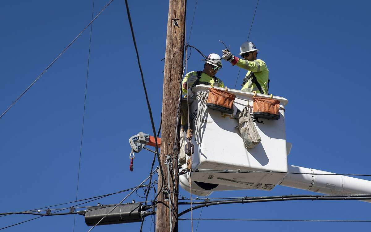 FILE - In this Oct. 25, 2019, file photo, Southern California Edison crews replace power lines that were damaged from the Tick Fire in Santa Clarita, Calif.