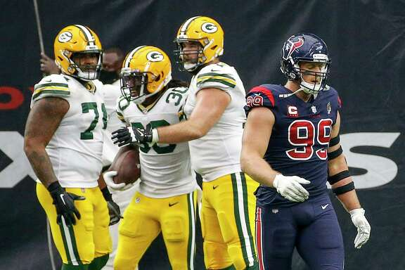 Houston Texans defensive end J.J. Watt (99) walks off the field as Green Bay Packers offensive guard Elgton Jenkins (74), running back Jamaal Williams (30) and offensive tackle Rick Wagner (71) celebrate a touchdown by Williams during the fourth quarter of an NFL game Sunday, Oct. 25, 2020, at NRG Stadium in Houston.