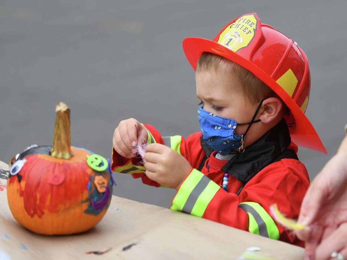 A boy decorates a pumpkin at the Westport Downtown Merchants Association Halloween Family Pumpkinfest in Westport, Conn. Sunday, Oct. 25, 2020. 150 families dressed in Halloween costumes participated in the socially-distant pumpkin painting event, presented by the Westport Parks & Recreation and Westport Police Athletic League in partnership with the WDMA.
