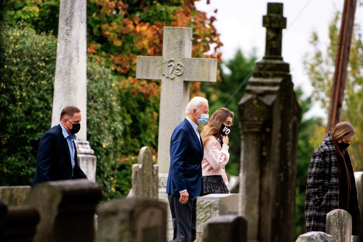 Joe Biden and his granddaughters Natalie and Finnegan Biden head toward a service at St. Joseph on the Brandywine in Wilmington, Del., on Sunday, Oct. 25, 2020.