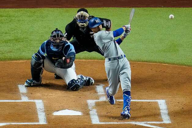 The Los Angeles Dodgers' Mookie Betts hits a leadoff double as Tampa Bay Rays catcher Mike Zunino works behind the plate during the first inning in Game 5 of the World Series at Globe Life Field in Arlington, Texas, on Sunday, Oct. 25, 2020. (Smiley N. Pool/Dallas Morning News/TNS) Photo: Smiley N. Pool, TNS
