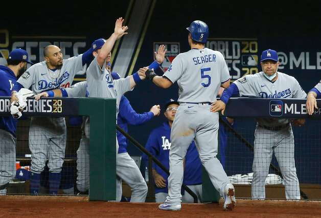 The Los Angeles Dodgers' Corey Seager (5) celebrates with teammates after scoring a run on a Cody Bellinger single against the Tampa Bay Rays during the first inning in Game 5 of the World Series at Globe Life Field in Arlington, Texas, on Sunday, Oct. 25, 2020. (Vernon Bryant/Dallas Morning News/TNS) Photo: Vernon Bryant, TNS