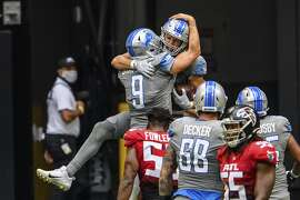 Detroit Lions tight end T.J. Hockenson (88) and quarterback Matthew Stafford (9) celebrate during the second half of an NFL football game against the Atlanta Falcons, Sunday, Oct. 25, 2020, in Atlanta. The Detroit Lions won 23-22. (AP Photo/Danny Karnik)