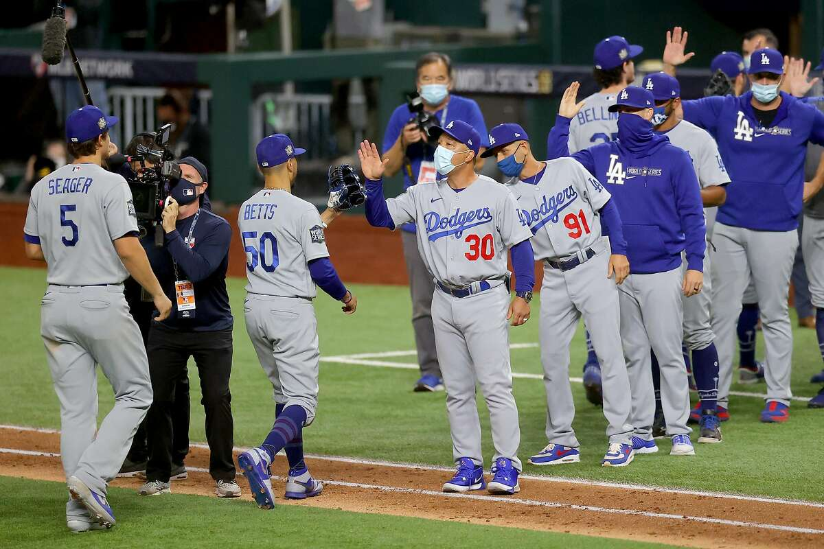 Manager Dave Roberts congratulates Mookie Betts #50 and Corey Seager #5 after the teams 4-2 victory against the Tampa Bay Rays in Game Five of the 2020 MLB World Series at Globe Life Field on October 25, 2020 in Arlington, Texas.