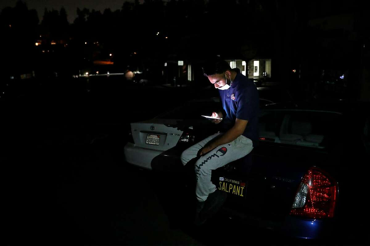 Moments after PG&E Public Safety Power Shutoff started, Mountain Mike Pizza employee Harry Virk sits on his car on Lasalle Avenue in Montclair neighborhood of Oakland, Calif., on Sunday, October 25, 2020. The pizza place closed early due to the PSPS that started at 8:45pm.