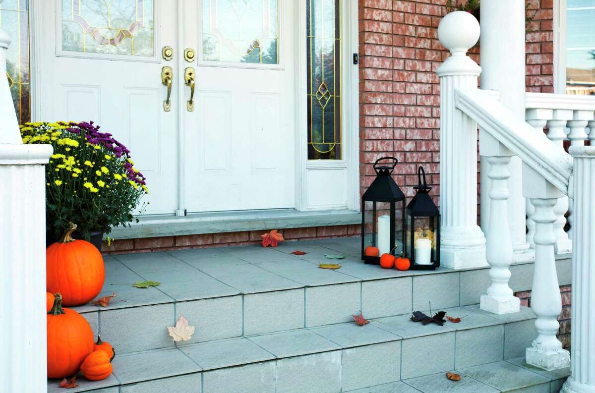 Pumpkins decorate the front porch of a traditional-styled home. (Photo by: Anjelika Gretskaia/REDA&CO/Universal Images Group via Getty Images)