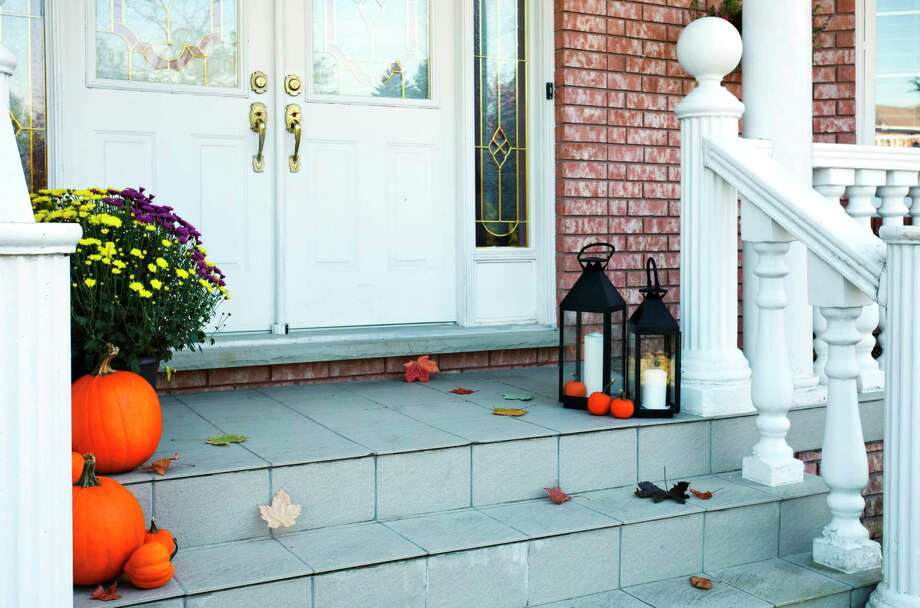 Pumpkins decorate the front porch of a traditional-styled home. (Photo by: Anjelika Gretskaia/REDA&CO/Universal Images Group via Getty Images) / Universal Images Group Editorial
