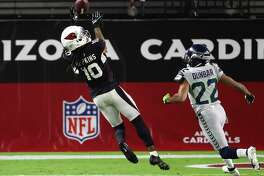 GLENDALE, ARIZONA - OCTOBER 25: Wide receiver DeAndre Hopkins #10 of the Arizona Cardinals makes a catch and runs for a touchdown as cornerback Quinton Dunbar #22 of the Seattle Seahawks looks on in the first quarter of the game at State Farm Stadium on October 25, 2020 in Glendale, Arizona.