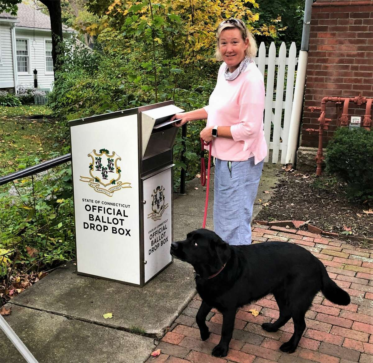Stephanie Johnson dropped off her absentee ballot at Guilford town hall last week, posing as her husband, Phil Johnson, captured the historic moment.
