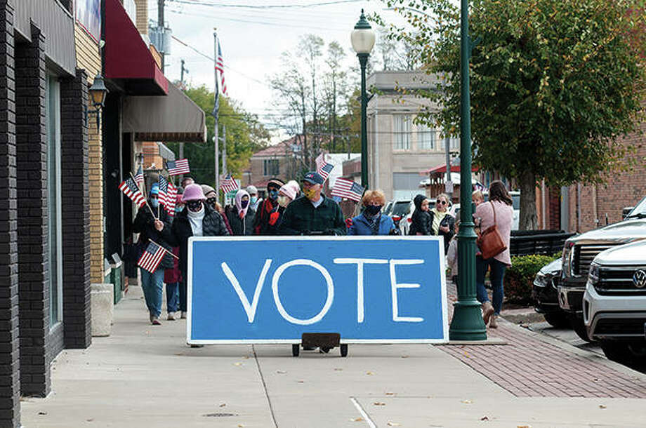 """A group walks from downtown Jacksonville toward the Morgan County Courthouse on Saturday as part of """"Stroll to the Poll."""" The event was organized by Morgan County Democrats to urge people to take advantage of early voting, regardless of party affiliation. For more photos, see the gallery at myjournalcourier.com. Photo: Darren Iozia 