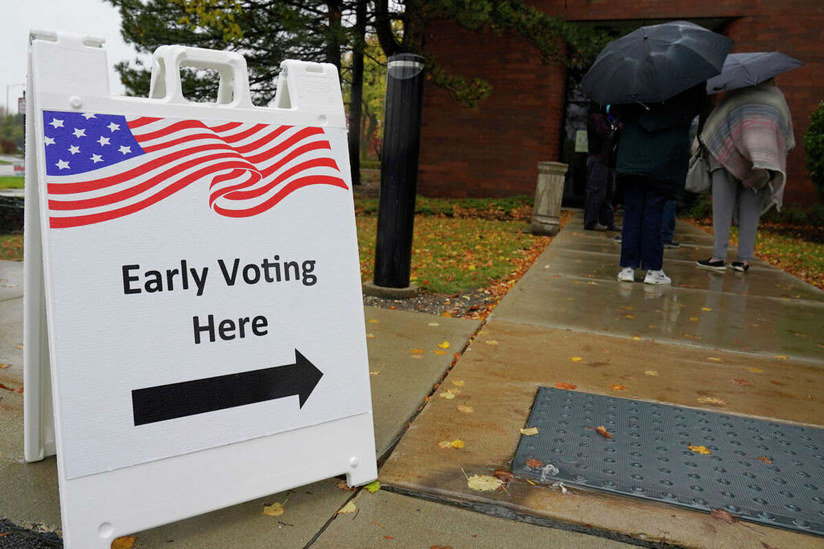 People wait in line during early voting on Friday.