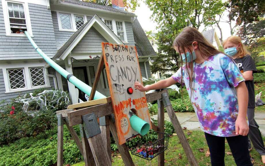 Neighbor Lucy White, 10, tests out the candy delivery chute (using PVC pipe) at the Dunn family home on Edgehill Road in New Haven, Conn., on Wednesday Oct. 21, 2020. The family created the chute system for kids to have a safe way to take part in Halloween. Photo: Christian Abraham / Hearst Connecticut Media / Connecticut Post