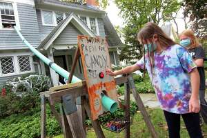 Neighbor Lucy White, 10, tests out the candy delivery chute (using PVC pipe) at the Dunn family home on Edgehill Road in New Haven, Conn., on Wednesday Oct. 21, 2020. The family created the chute system for kids to have a safe way to take part in Halloween.