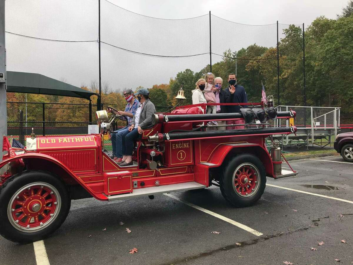 Tom Stadler holds his granddaughter, Kate, in the back of an Old Faithful antique fire engine, flanked by his wife, Jan, and son, Sean, in Mead Park Friday, Oct. 23, when a party was held in honor of his retirement.