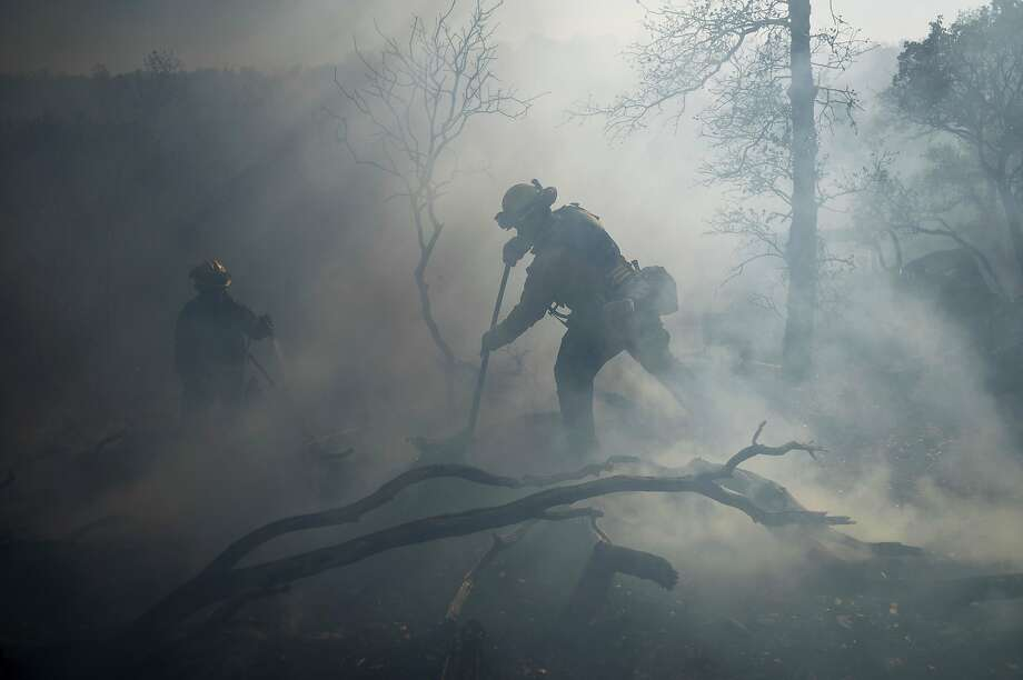 A firefighter extinguishes hot spots while battling the Olinda Fire in Anderson, Calif., on Sunday The blaze was one of four fires burning near Redding that firefighters scrambled to stop as high winds buffeted Northern California. Photo: Noah Berger / Associated Press