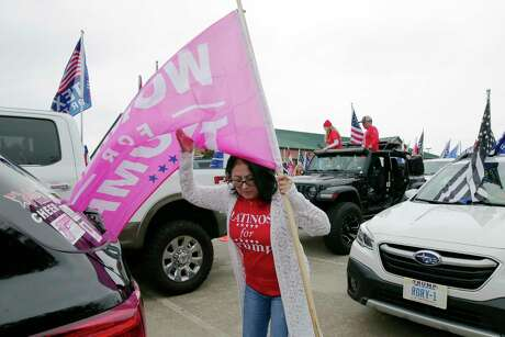 """Hope Cruz wrangles a """"Women for Trump"""" flag against the wind as she and other Trump supporters gather at the Montgomery County Constable offices parking lot before the start of the """"Magnolia Trump Train Parade"""" Saturday, Oct. 17, 2020 in Magnolia, TX."""