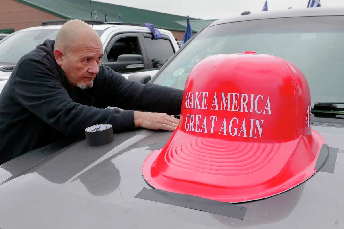 Roy Vee tapes down a plastic MAGA hat to the hood of his pick up truck at the Montgomery County Constable offices parking lot before the start of the