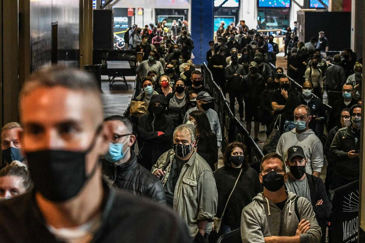 Masked New Yorkers wait in a line to vote at Madison Square Garden during early voting for the U.S. presidential election on Oct. 24, 2020, in New York City. Due to the coronavirus and social-distancing concerns, New York State is allowing early voting for the first time.