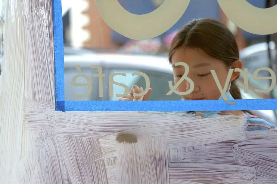 Jingjing He, 11, of Darien, paints the window of UCBC on the Post Road on Saturday morning. Photo: Jarret Liotta For Hearst Connecticut Media / ©Jarret Liotta 2020