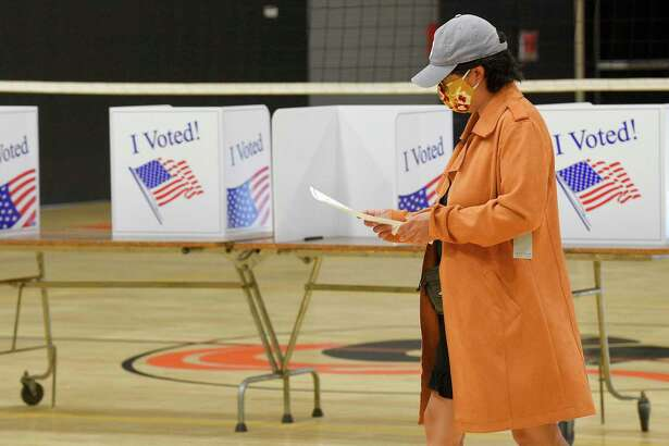File photo of a voter checking over a ballot after the presidential primary election in Stamford, Conn., on Aug. 11, 2020.