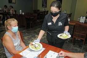 Bluff City Grill server Olivia Bromaghim delivers salads to the table of mask-wearing customers in Alton on Aug. 29. Illinois has again restricted indoor dining in Madison County and other Region 4 bars and restaurants starting Wednesday.