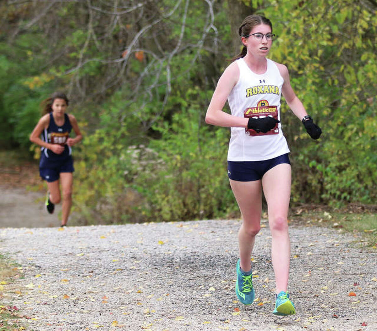 Roxana's Riley Doyle (right) leads Father McGivney's Kaitlyn Hatley out of the wooded area at Loveless Park in the final mile of the Carlinville Class 1A Regional on Saturday morning. Hatley surrendered second place in the race to Doyle when taking a wrong turn earlier in the course.