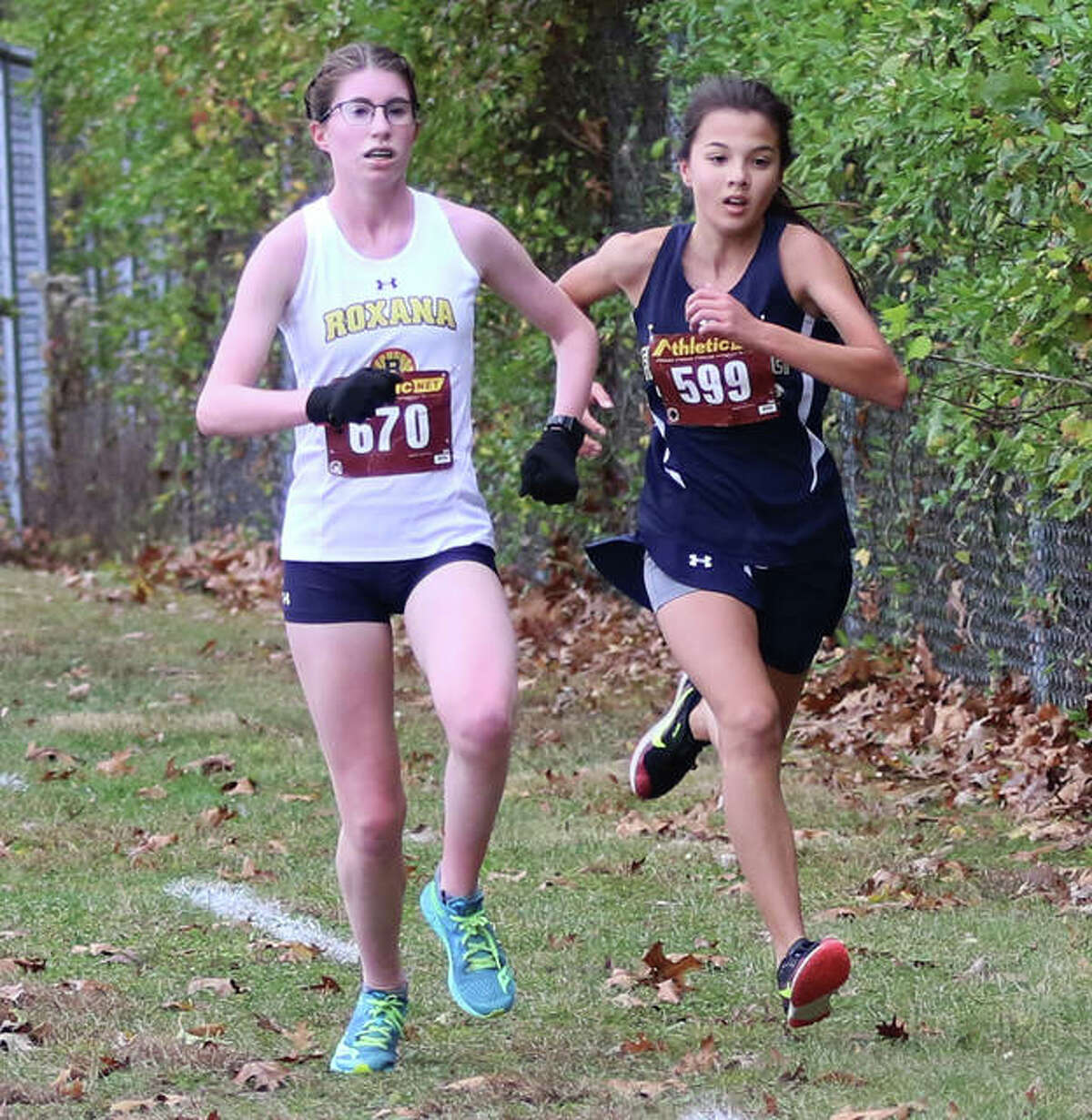 Father McGivney's Kaitlyn Hatley (right) pushes past Roxana's Riley Doyle in a push to the finish Saturday at Loveless Park in the Carlinville Class 1A Regional.