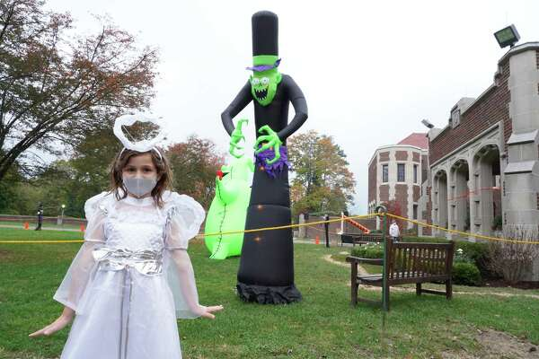 """Juliet Casey dressed as an angel during the New Canaan Recreation Department's """"Halloween Happenings Outdoor Family Walk"""" Friday, Oct. 23, 2020 at Waveny Park. There were several large blown up spooky characters on the mansion lawn."""