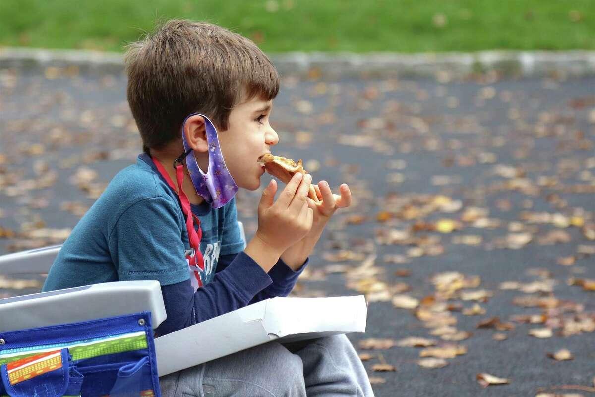 Benjamin Boselli, 6, of Westport, enjoys some pizza at the MoCA Westport on Saturday, Oct. 24, 2020, in Westport, Conn.