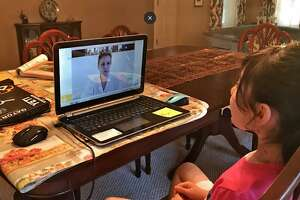 In this file image, a Fort Bend ISD students engages with a teacher online in a video posted to the district website.