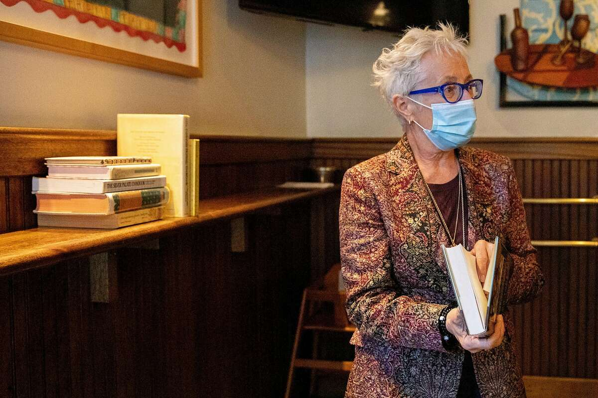 """Chef Cindy Pawlcyn looks through a cookbook titled """"Outlaw Cook"""" by John Thorne given to her by long-time friend Nickie Zeller while at Mustards Grill in Napa, Calif. Saturday, October 24, 2020."""